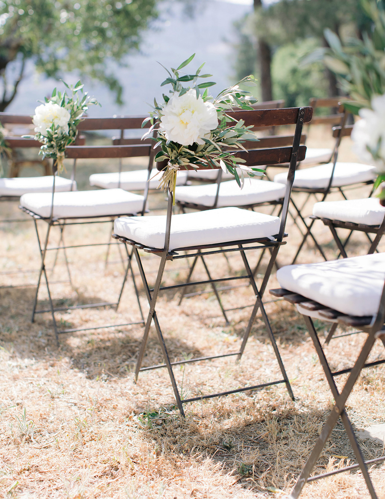 wedding ceremony chairs white seat cushions and flowers