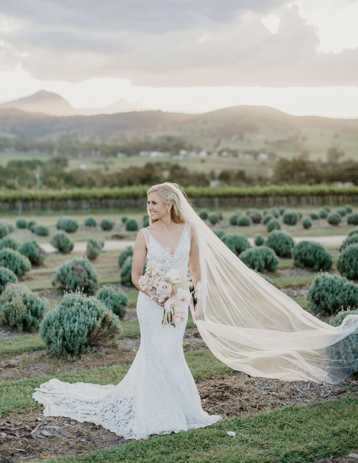 bride holding bouquet in field of greenery