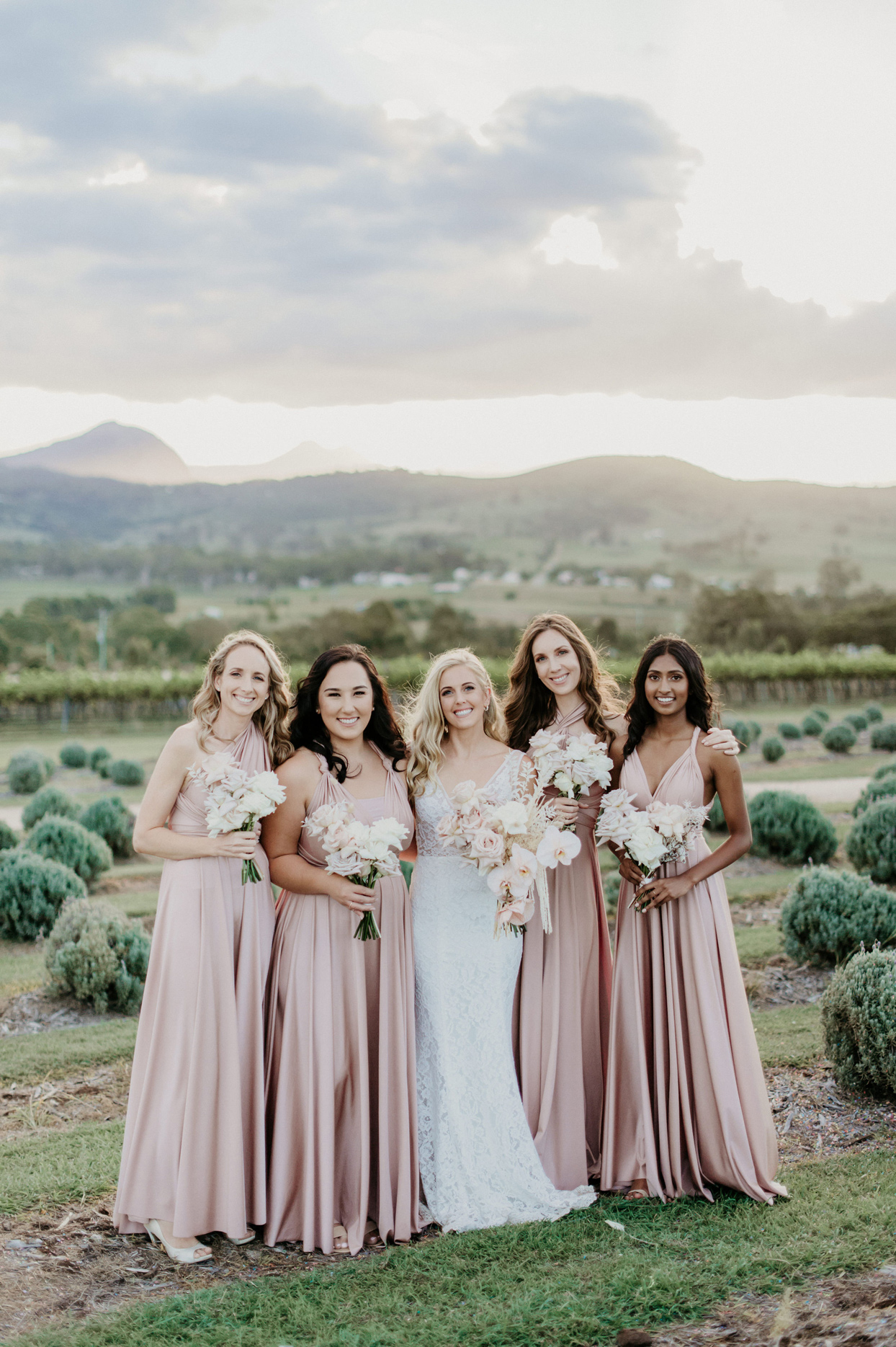 bride with bridesmaids wearing dusty pink long drersses