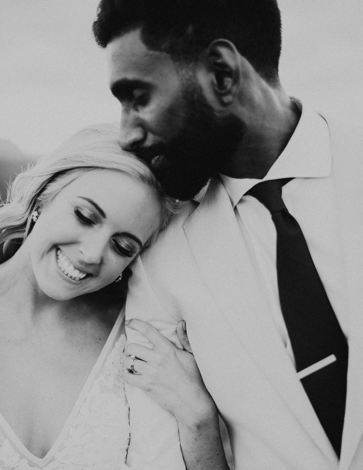 groom kisses smiling bride on the top of her head