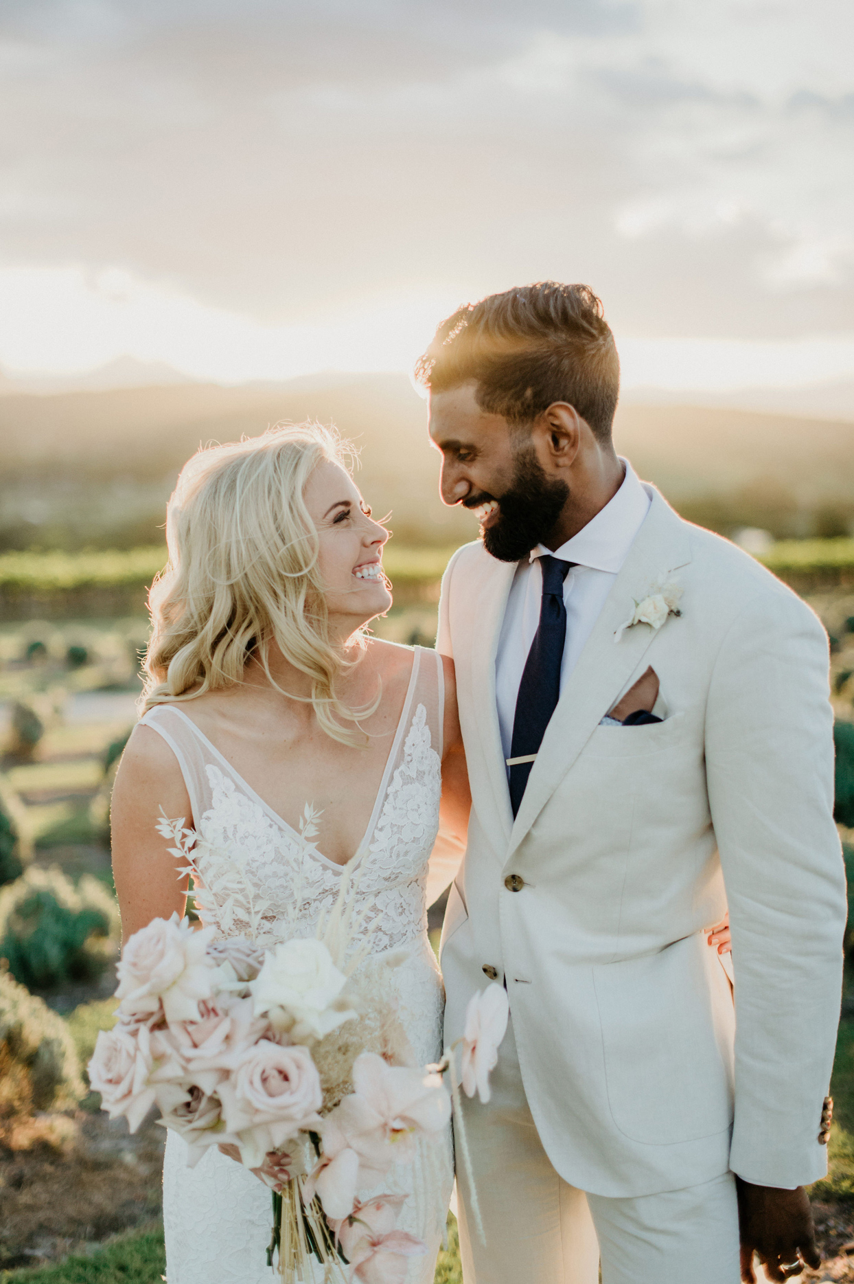 bride and groom smile at each other with sun shining behind them