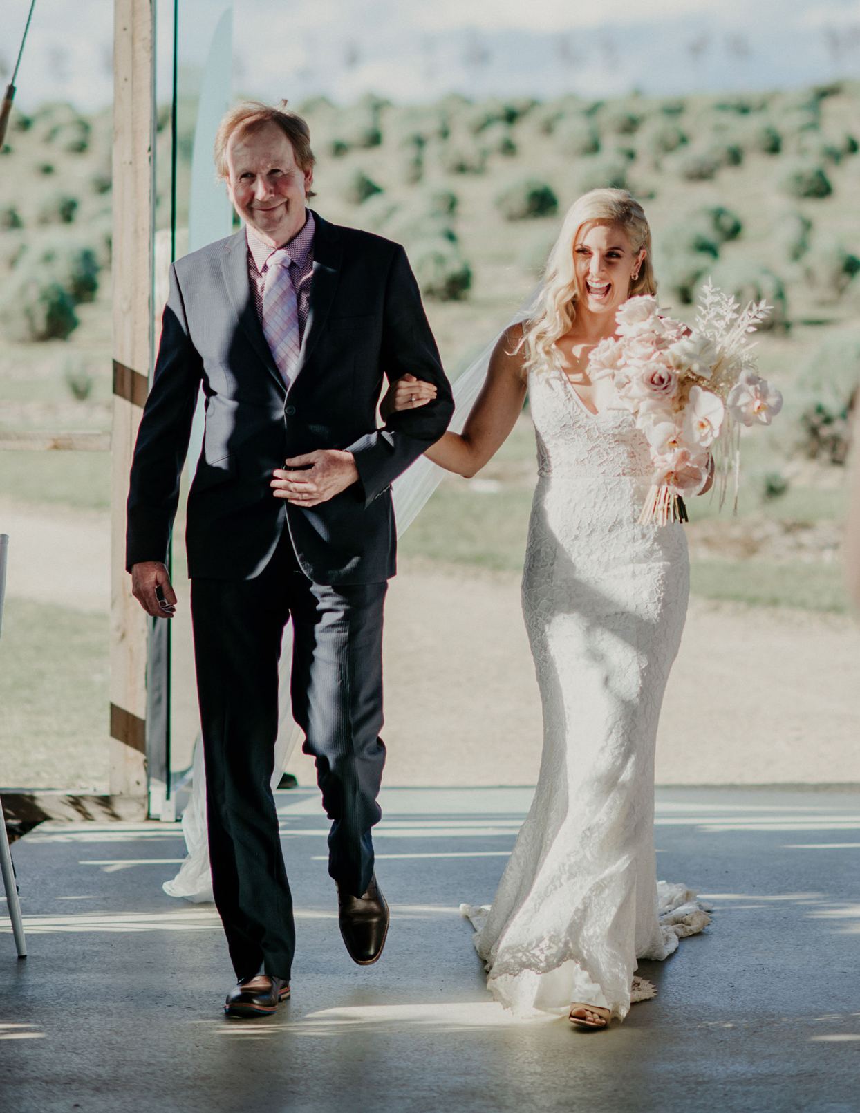 bride smiles as father walks her down the aisle