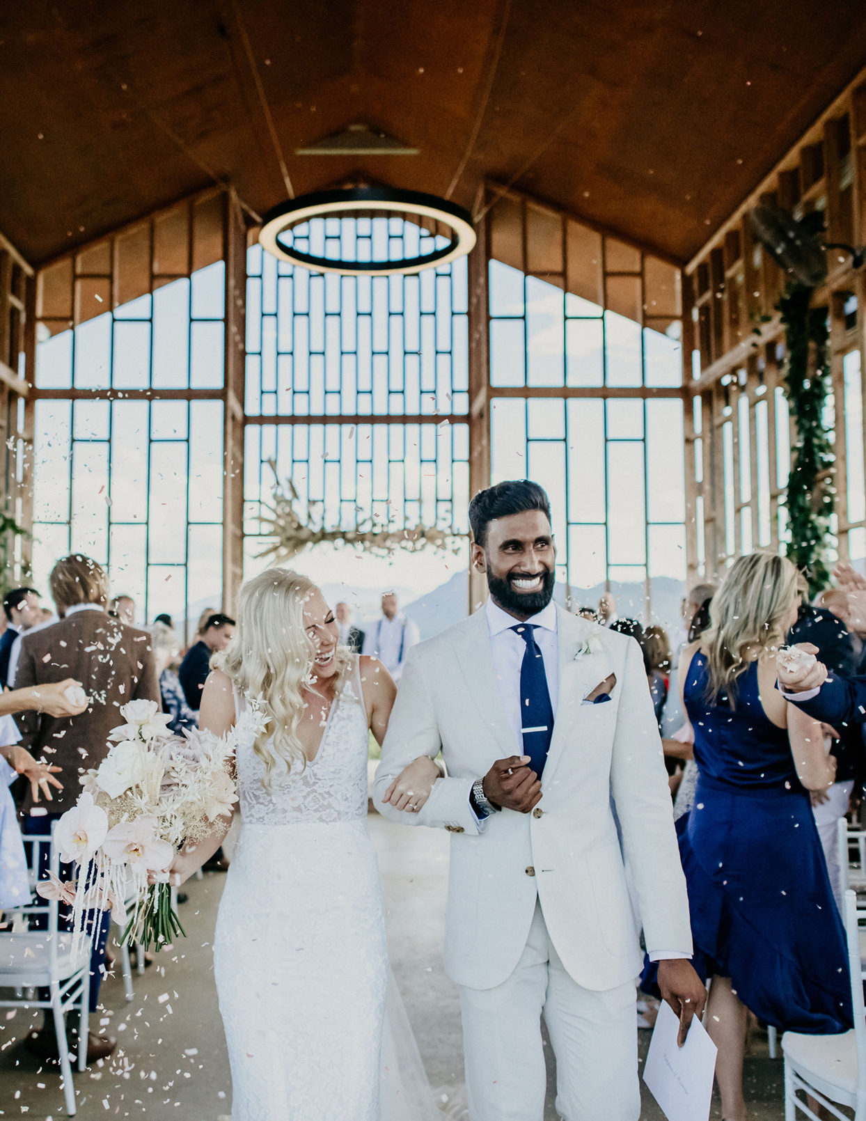 bride and groom smile walking down recessional aisle