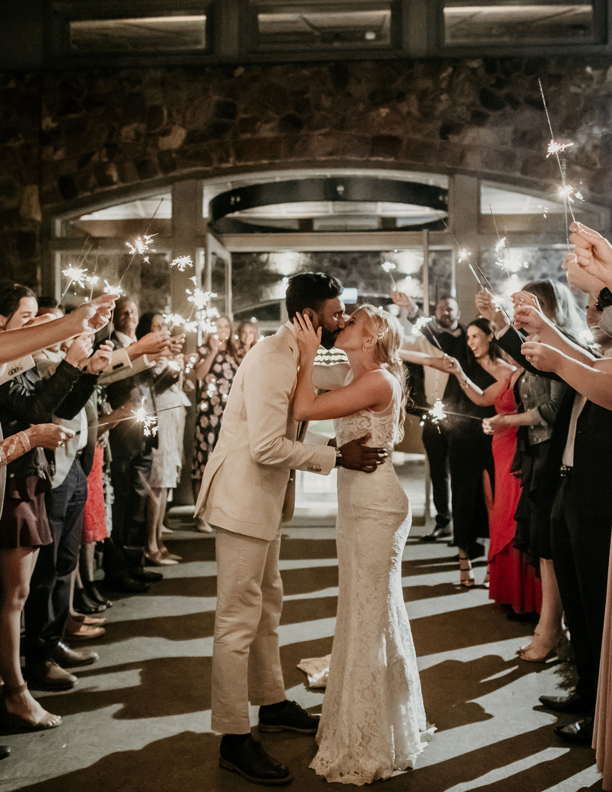 bride and groom kiss under guests holding sparklers