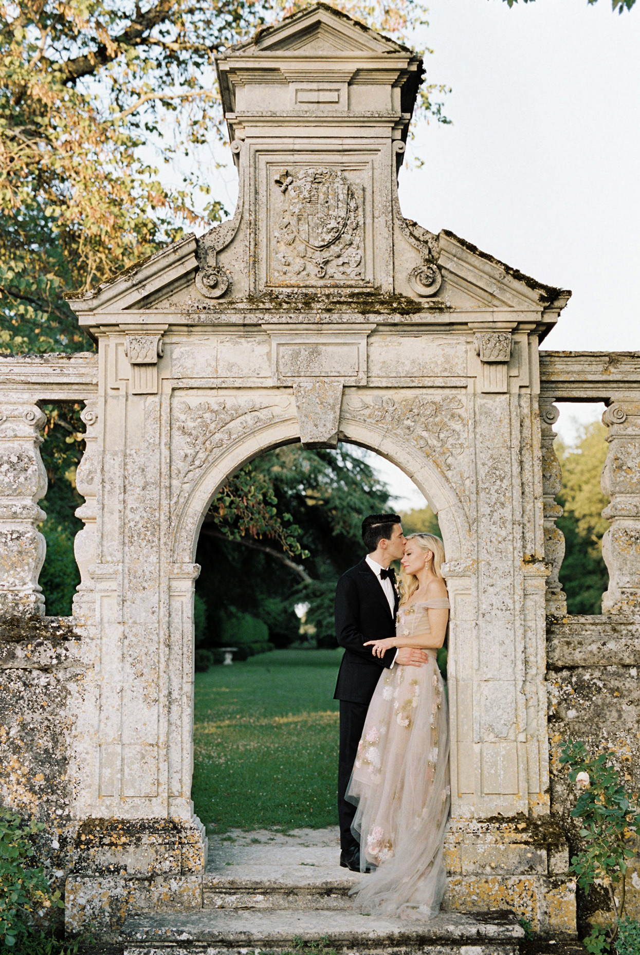wedding couple under romantic outdoor stone arch