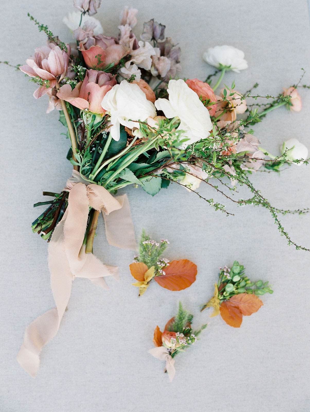 pastel and white colored flowers with greenery wrapped with light pink raw edge ribbon