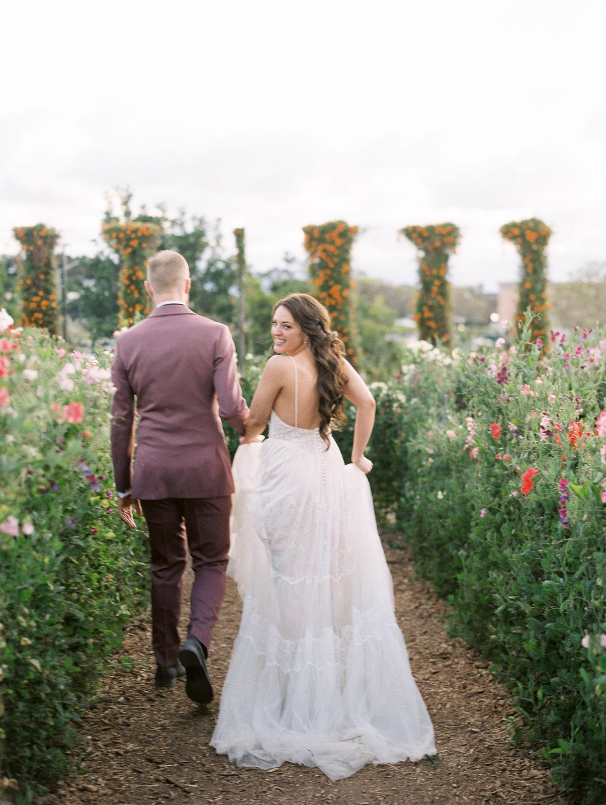 bride and groom walking through garden bride looking back smiling
