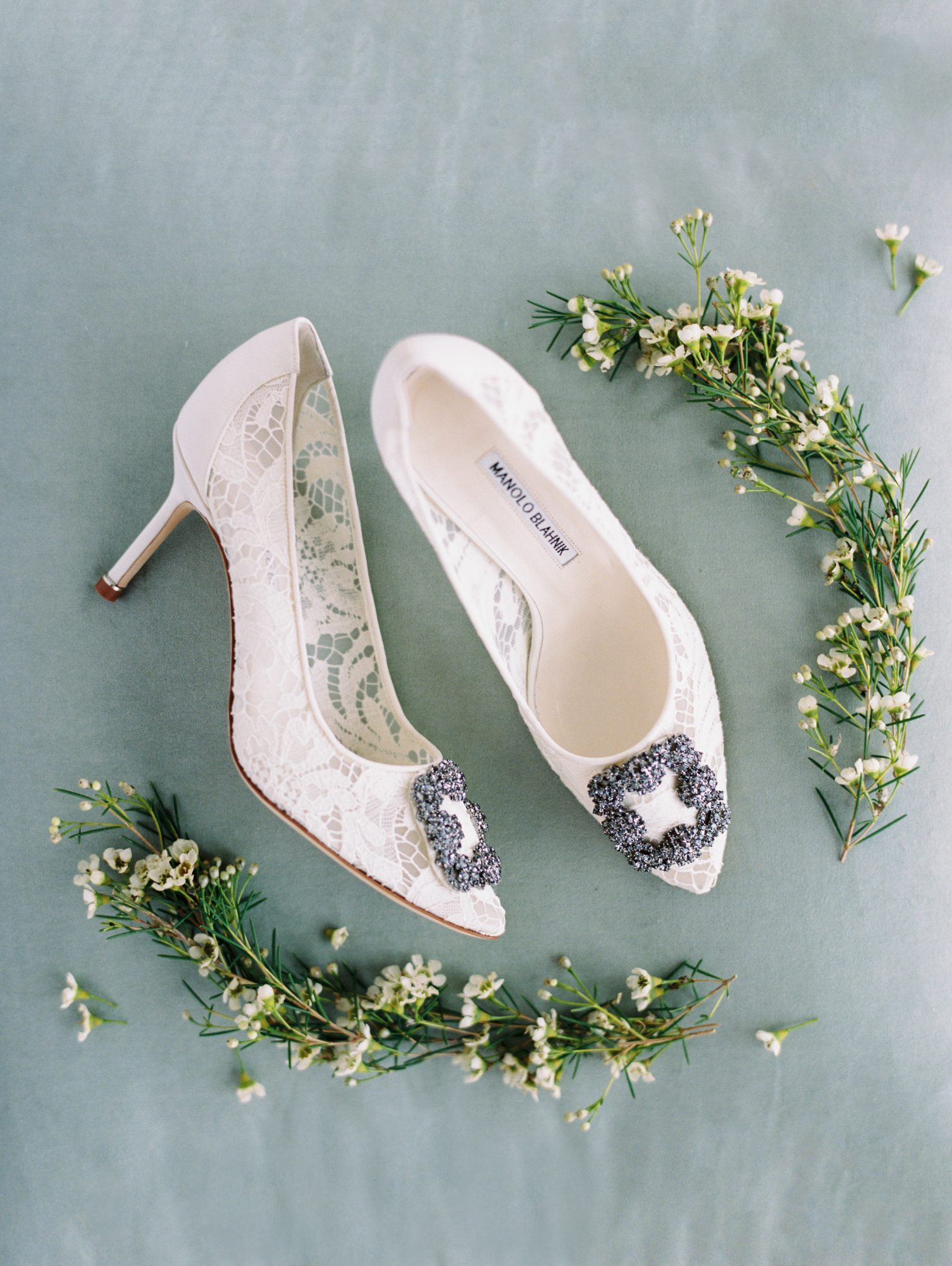 erinn andrew wedding bride shoes surrounded by greenery
