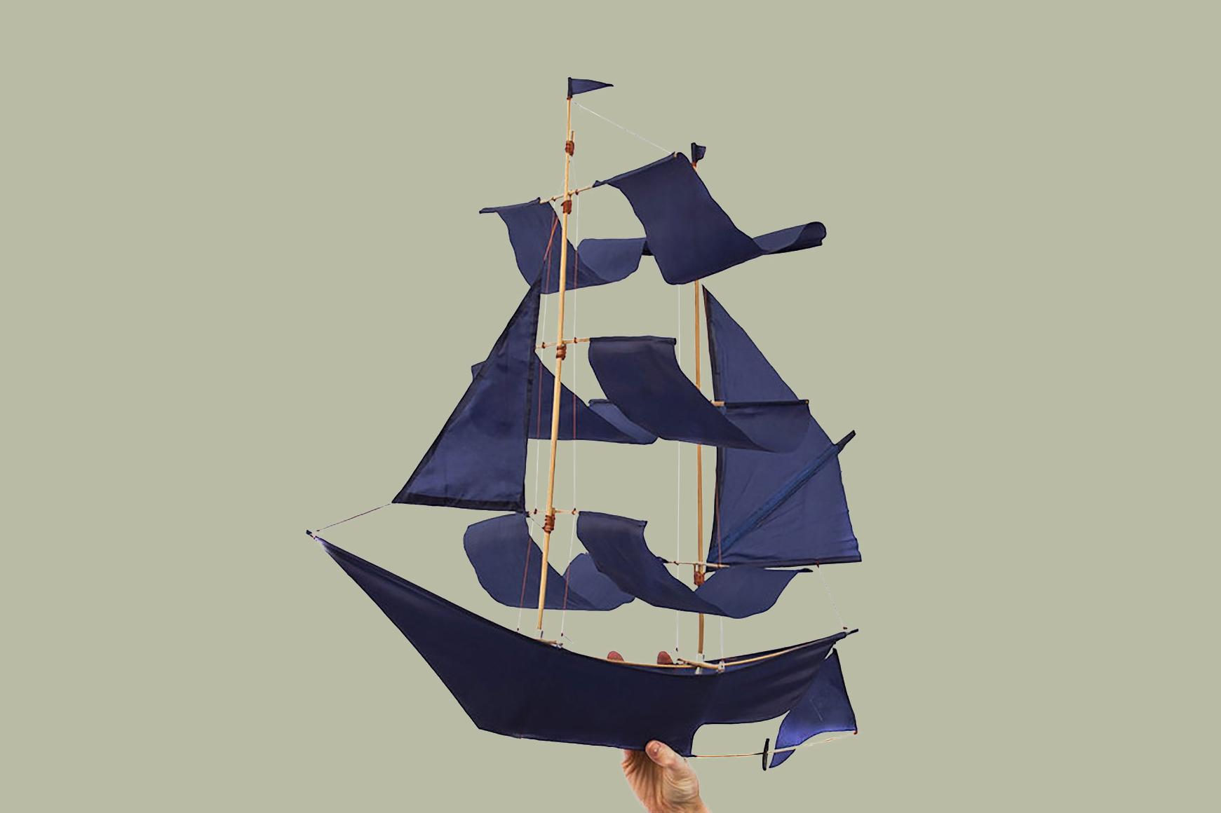 hand holding sail boat kite