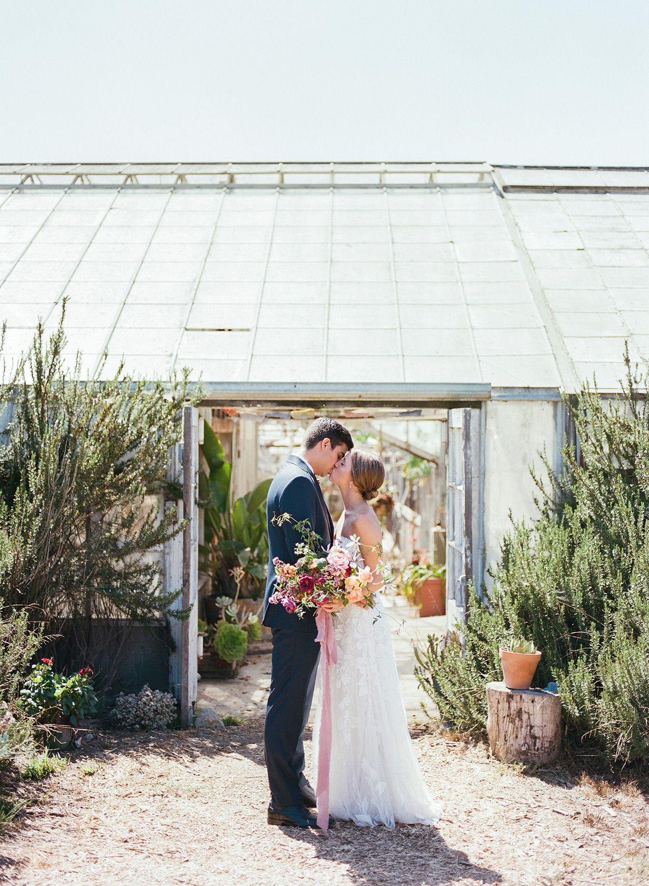 bride groom kiss outdoors greenhouse