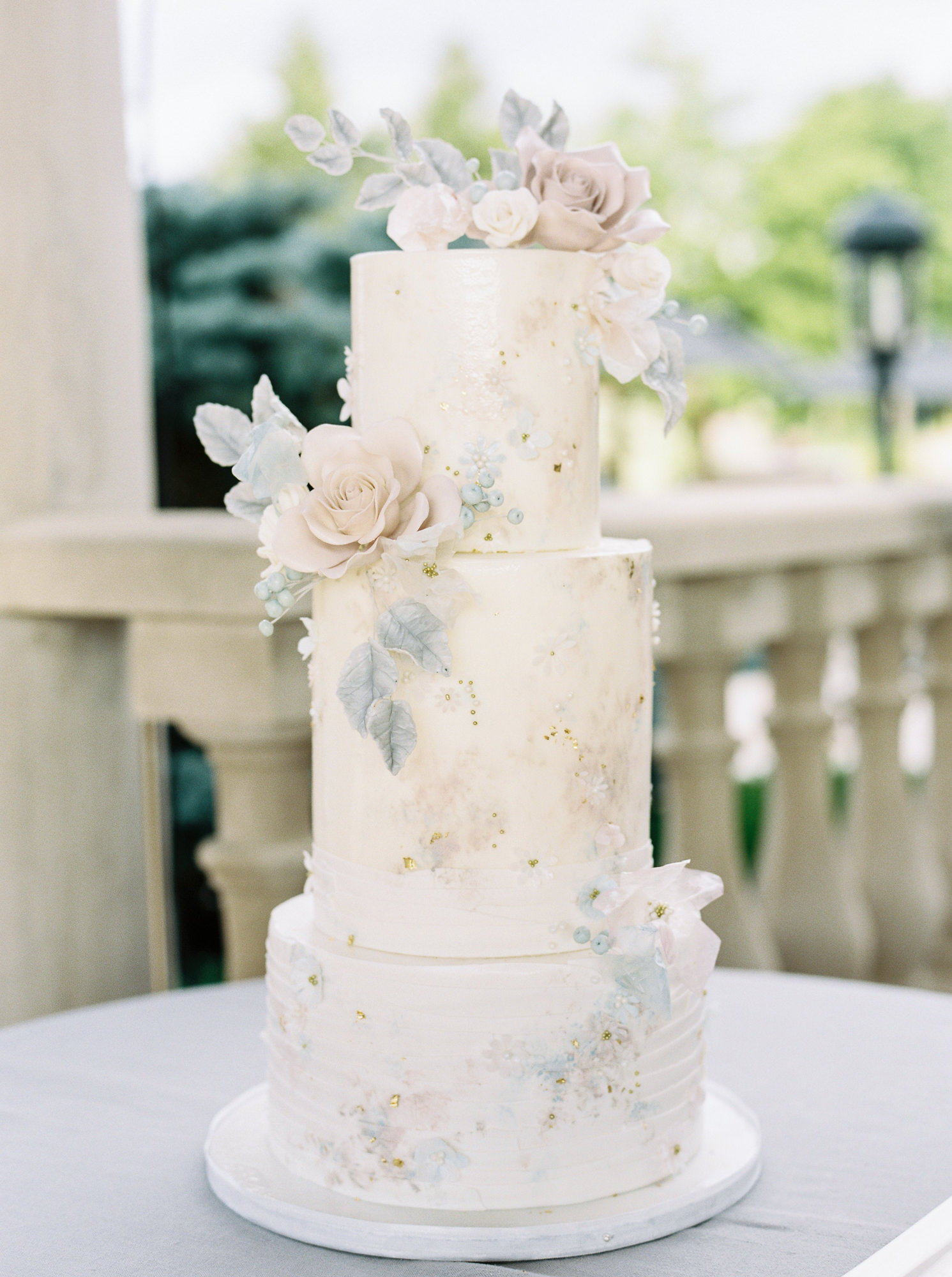 three tiered white wedding cake with blush, dusty blue, and taupe sugar flowers