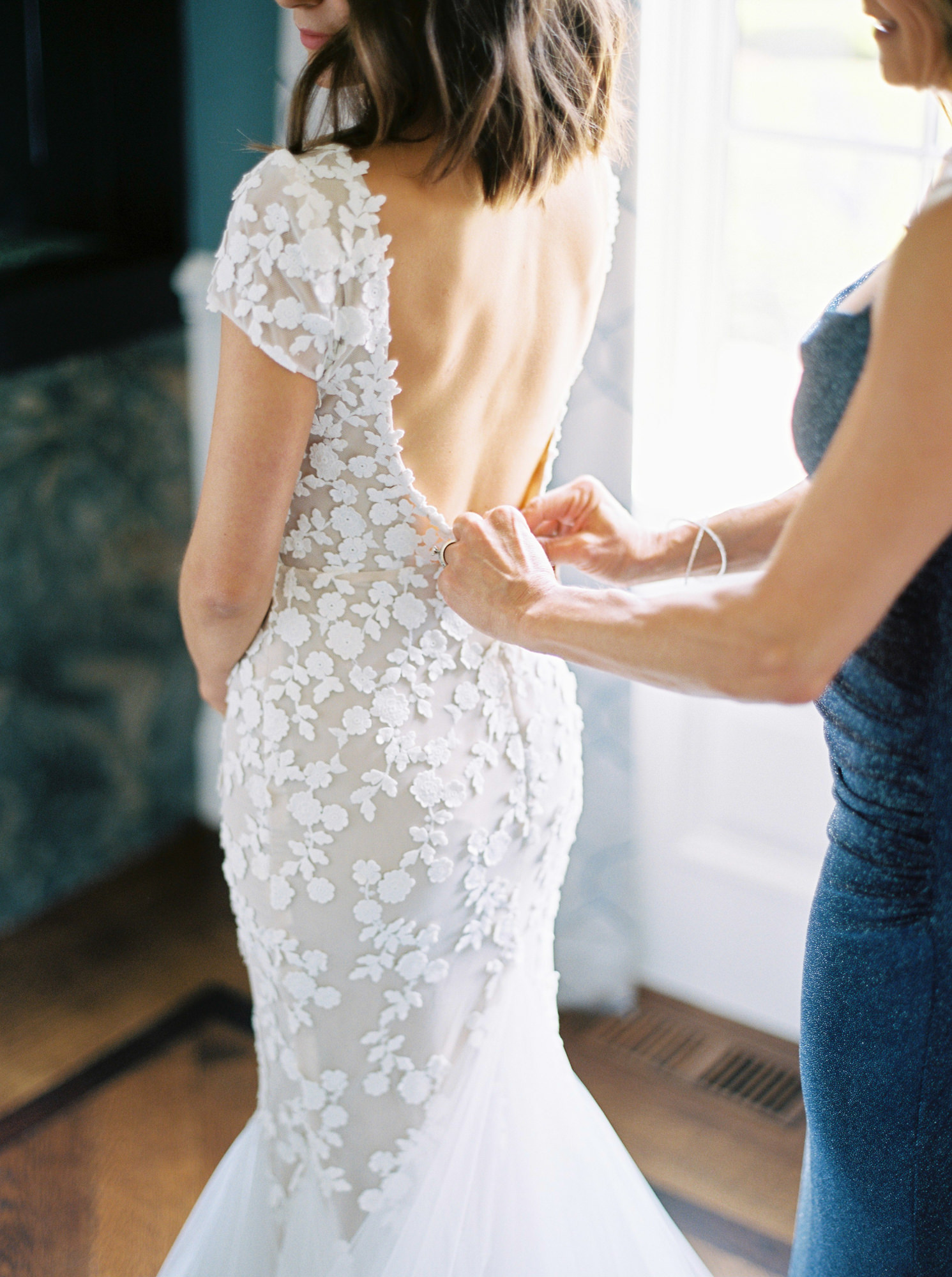 mother of the bride buttoning Liz Martinez Sophia gown on bride