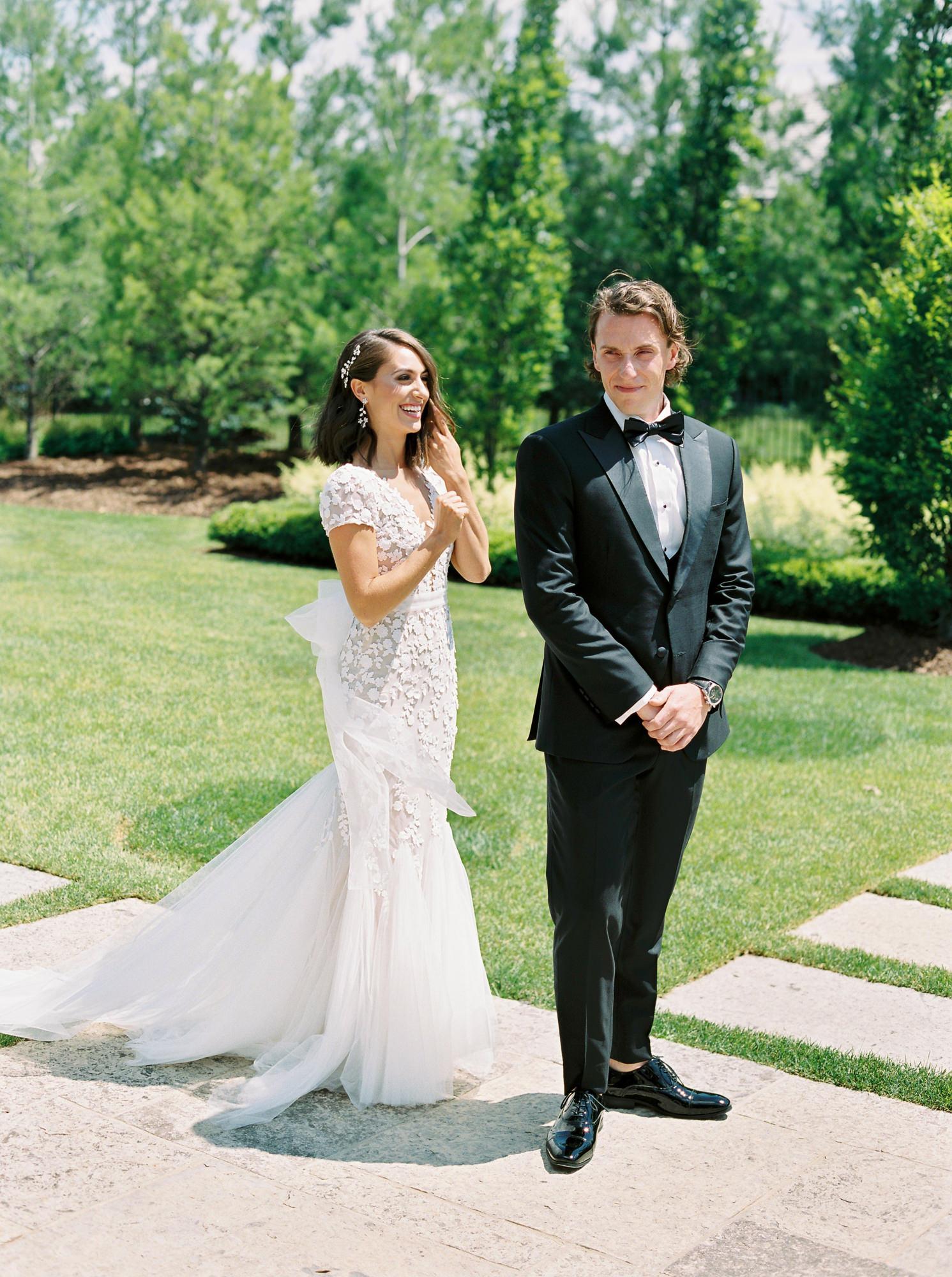 bride standing behind groom outside before first look