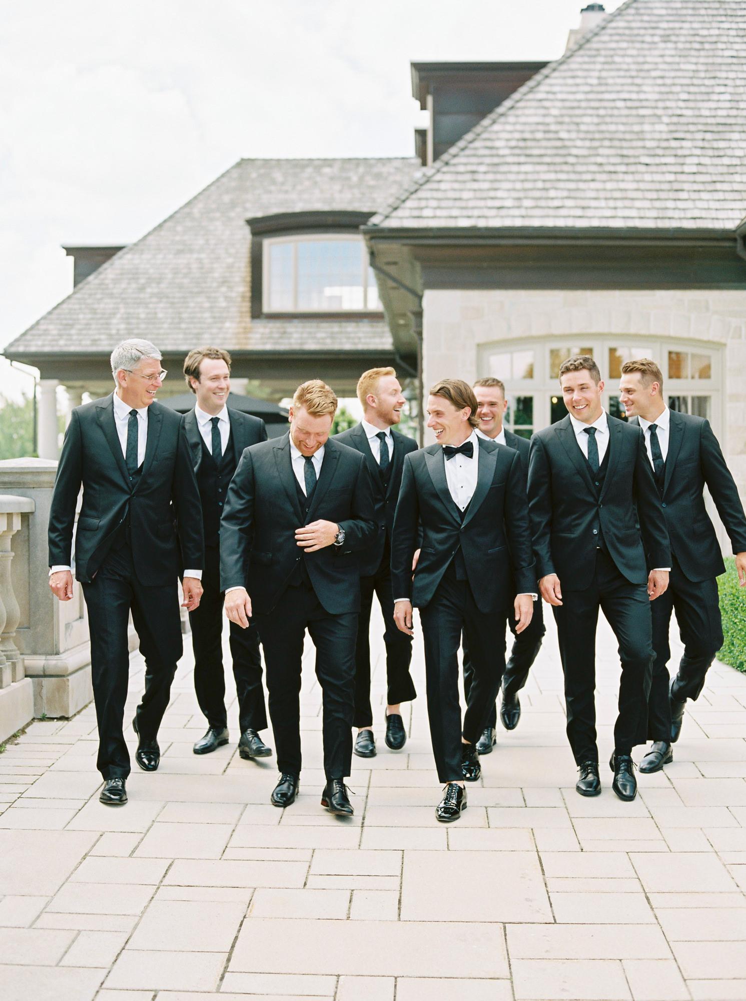 groom with groomsmen smiling all wearing black suits
