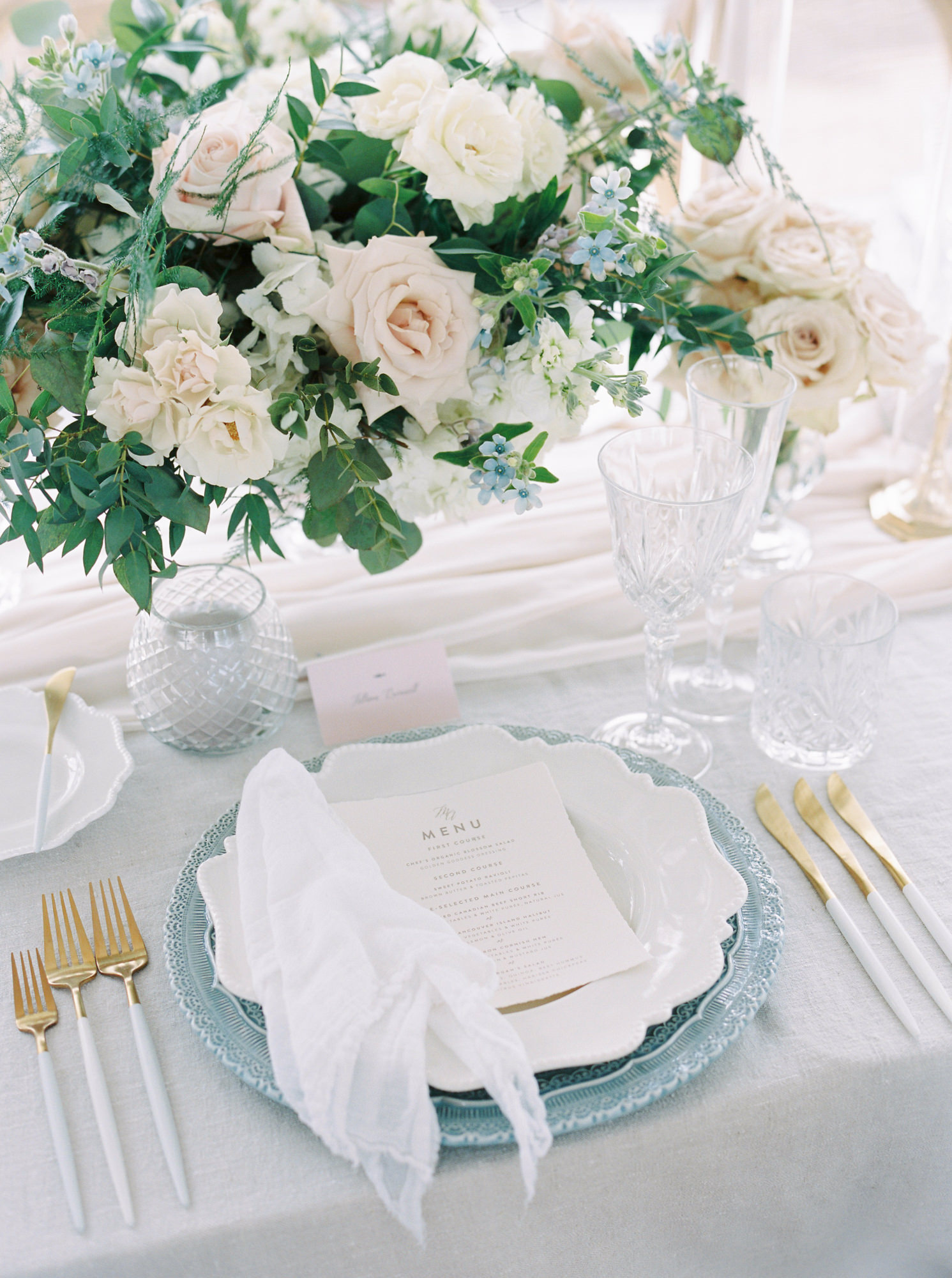 blue charger white plate placesetting with gold and white silverware and glass china