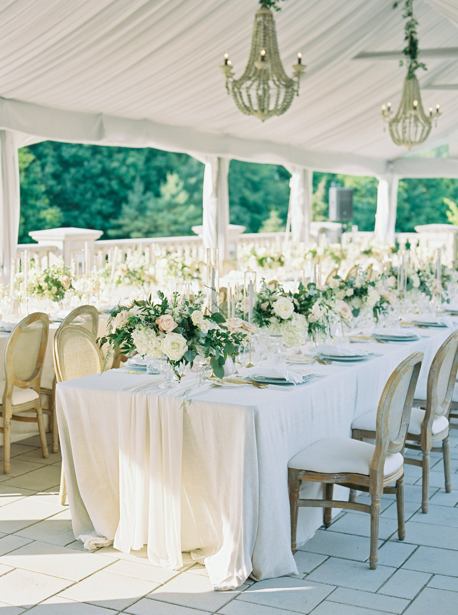 white linen covered reception tables with white and green floral centerpieces