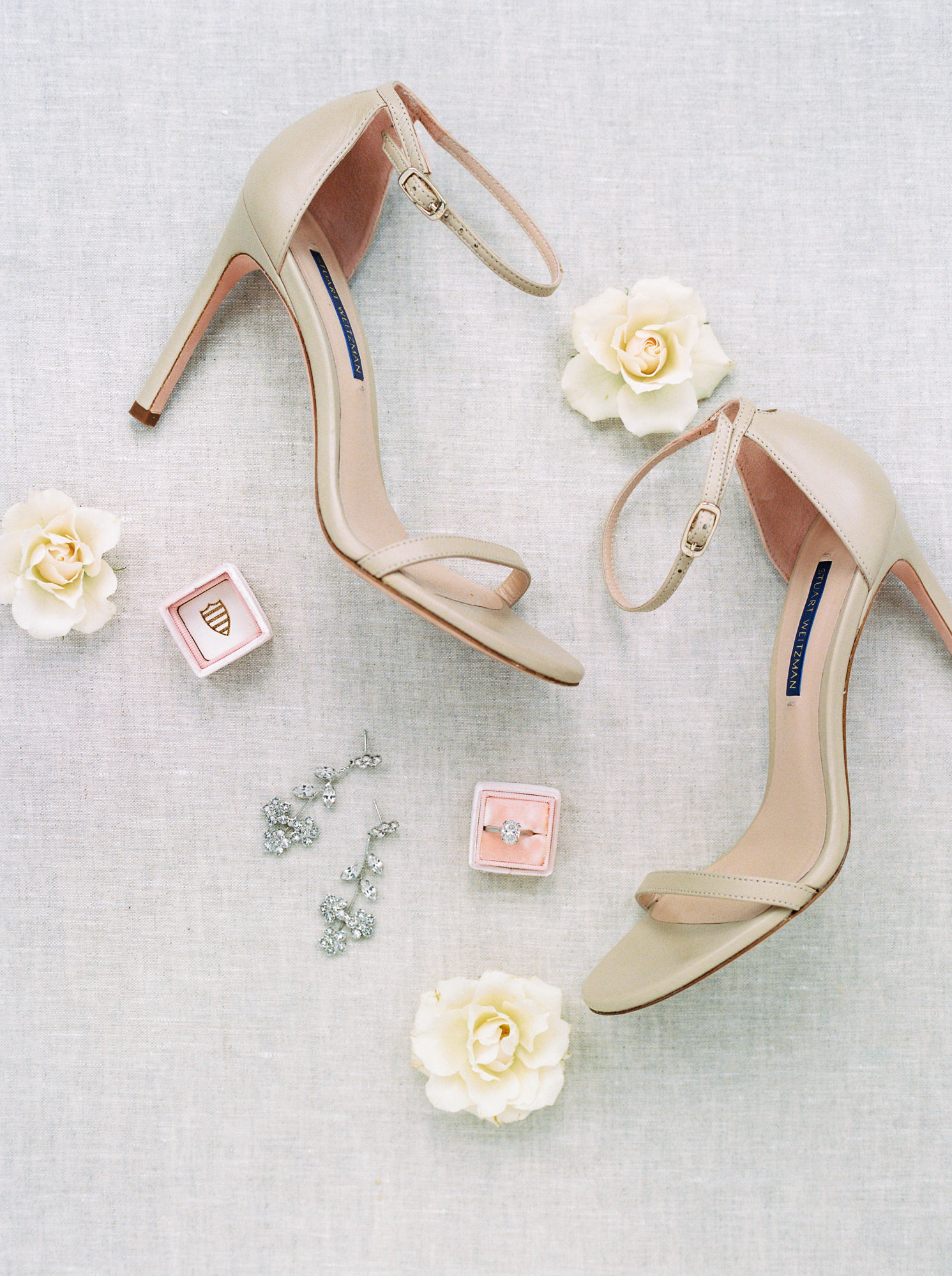 nude ankle-strap Stuart Weitzman heels with dangly diamond and silver earrings