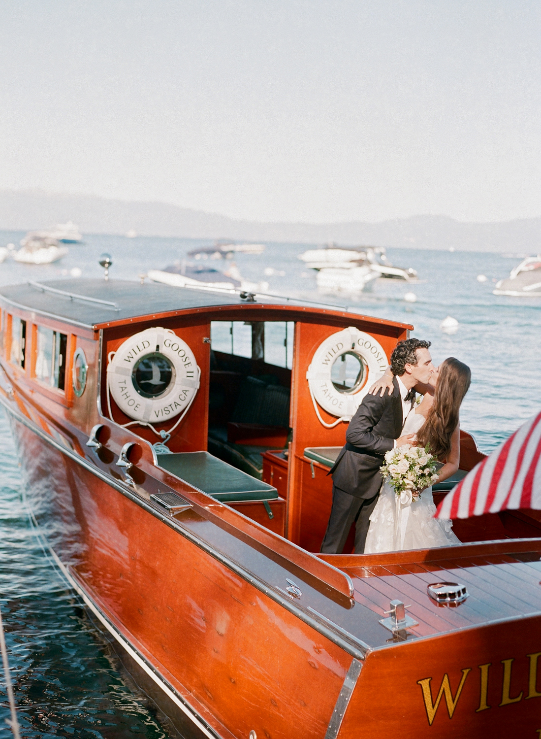 Natalie and Grant wedding couple kissing on red boat on lake