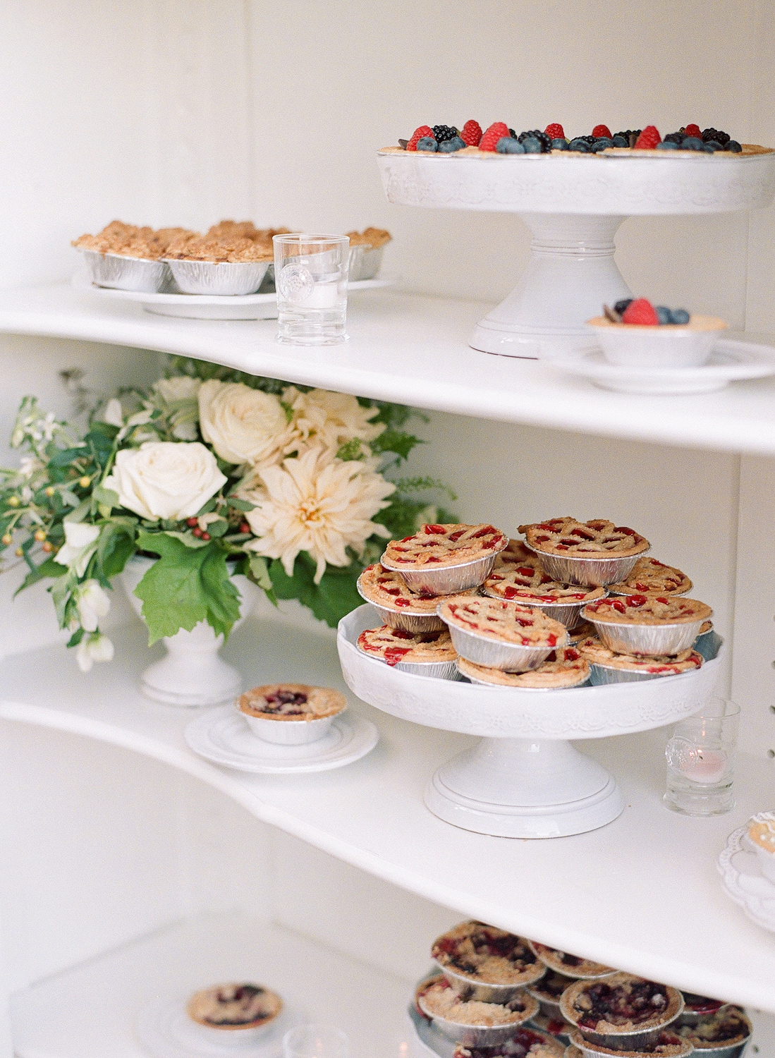 Natalie and Grant wedding miniature pies on shelf near flowers