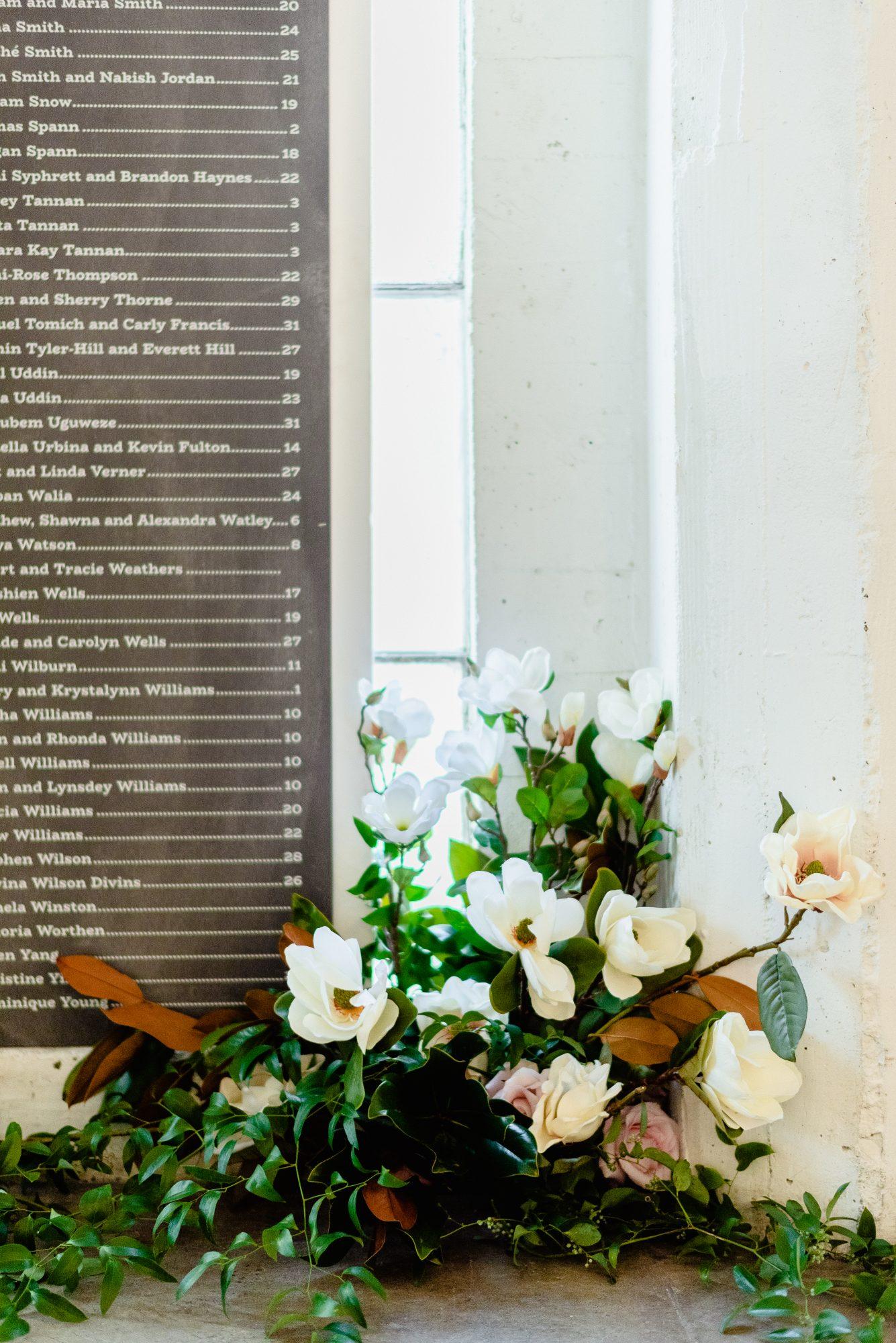 ryan shep wedding seating chart next to flowers