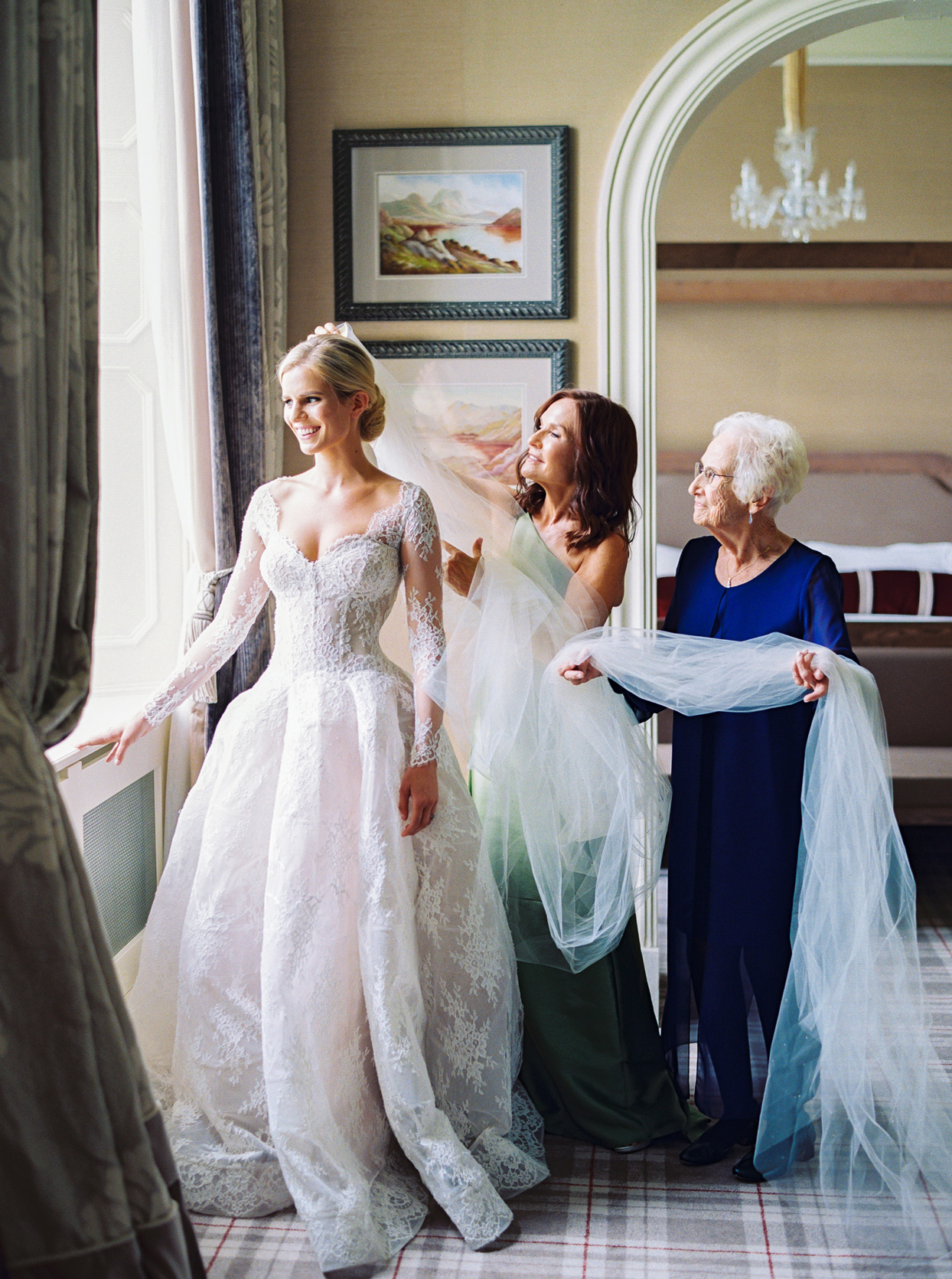 mother and grandmother of the bride putting the bride's veil on