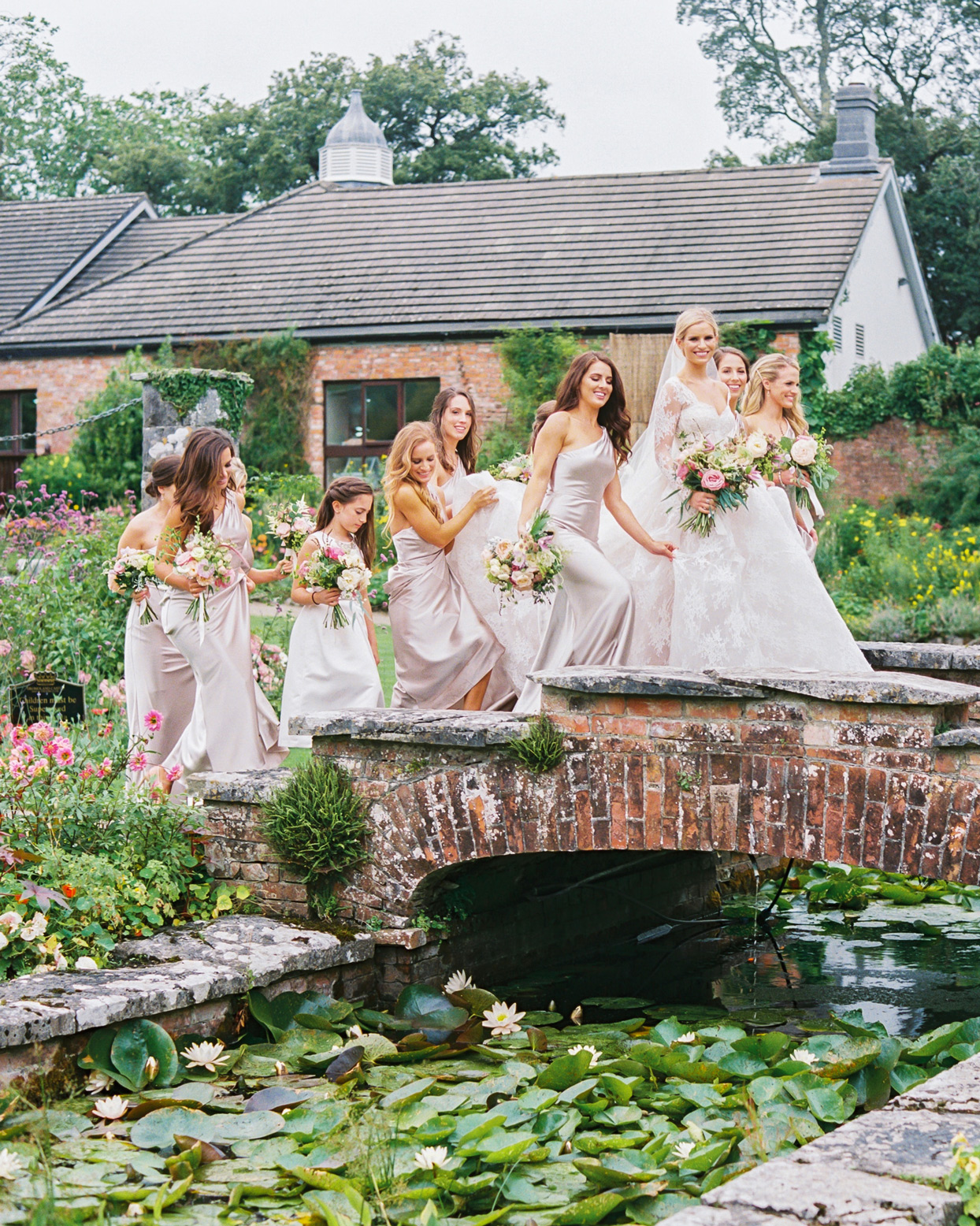 bride and bridesmaids waking over brick bridge over lily pond