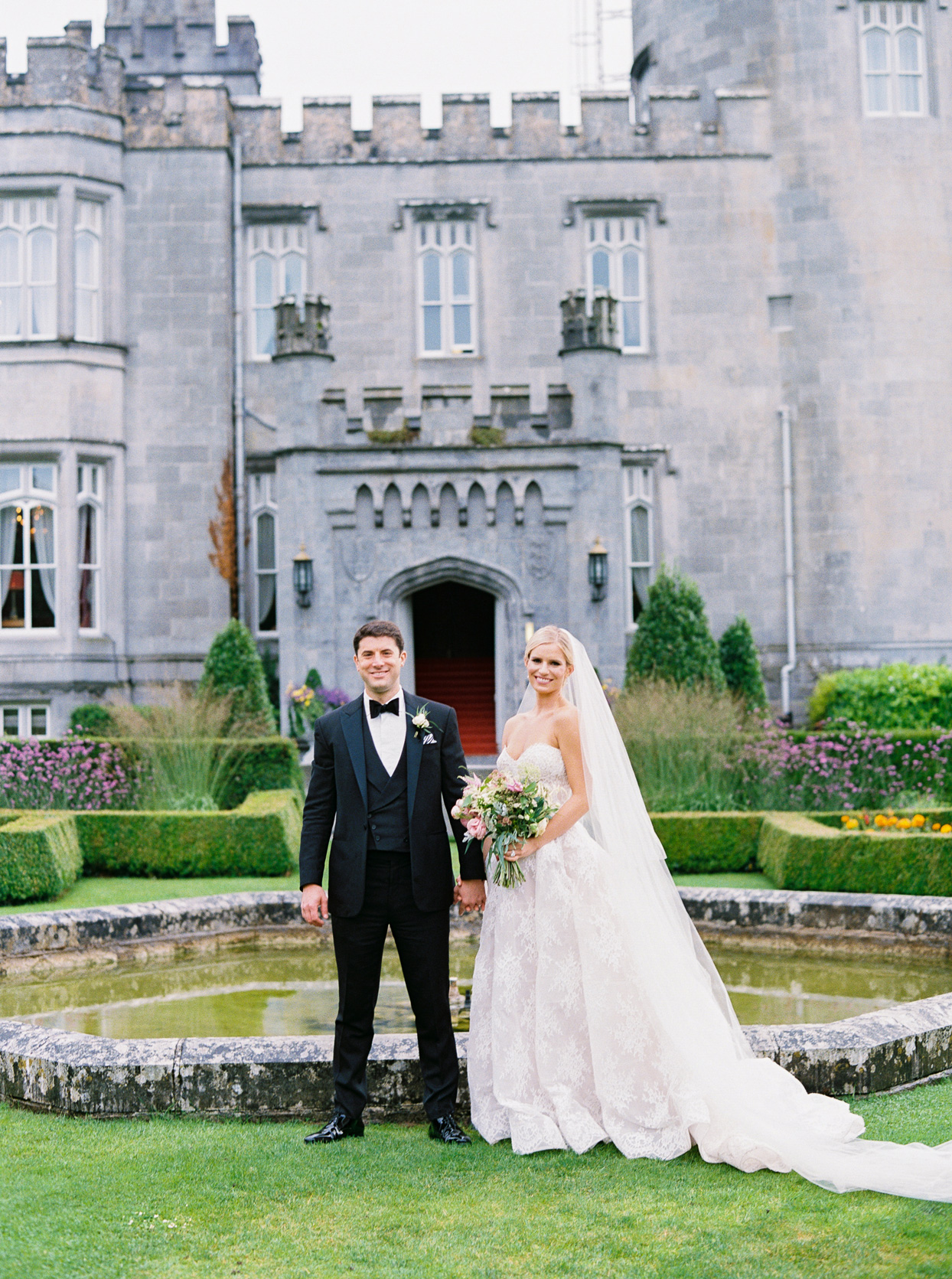 bride and groom standing in front of the Dromoland Castle