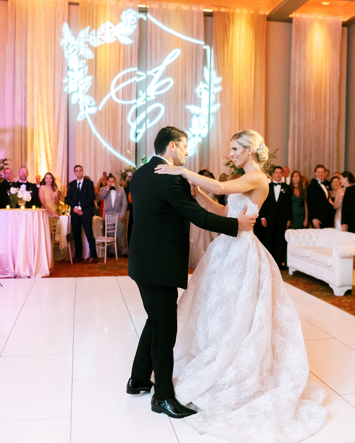 bride and groom share first dance on white tile dance floor surrounded by guests
