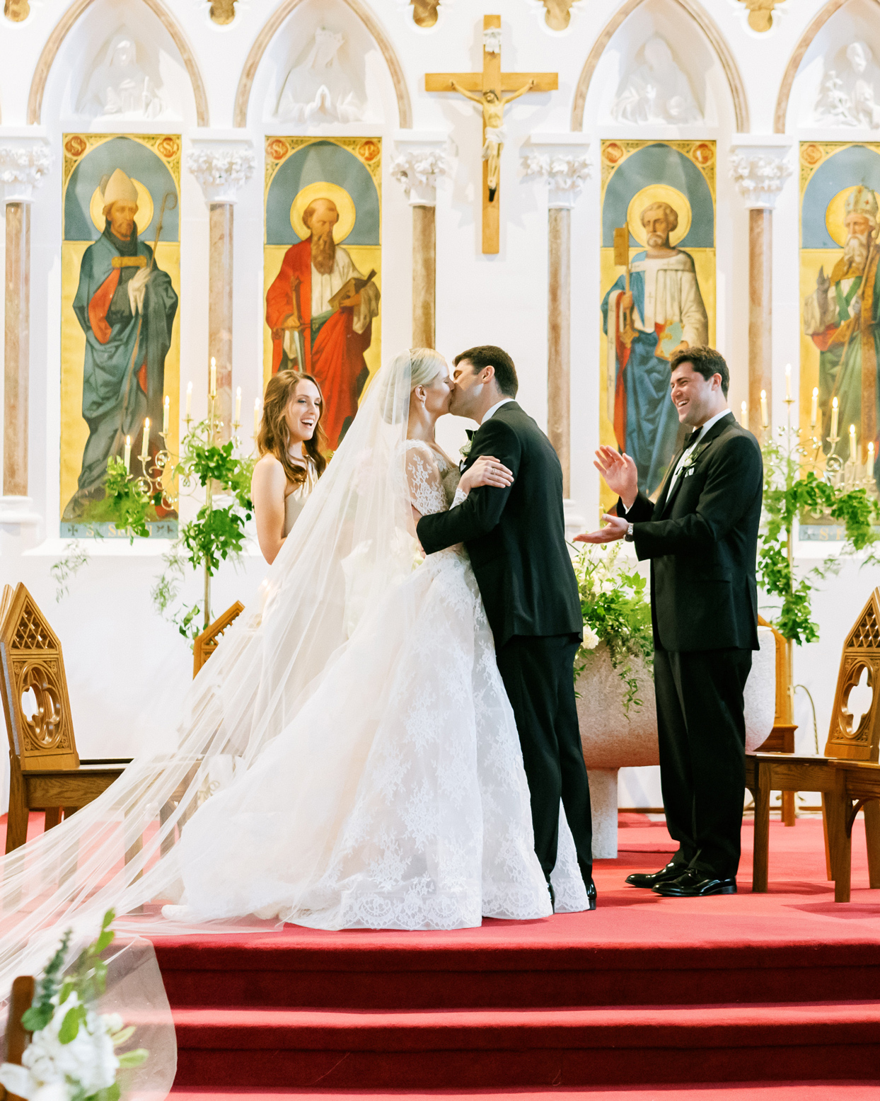 bride and groom kiss during wedding ceremony in church