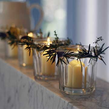 BHGDec04_Four votive candles in glass holders with pine garland