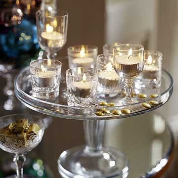BHGDec04_Glass serving tray with votive candles inside crystal glasses