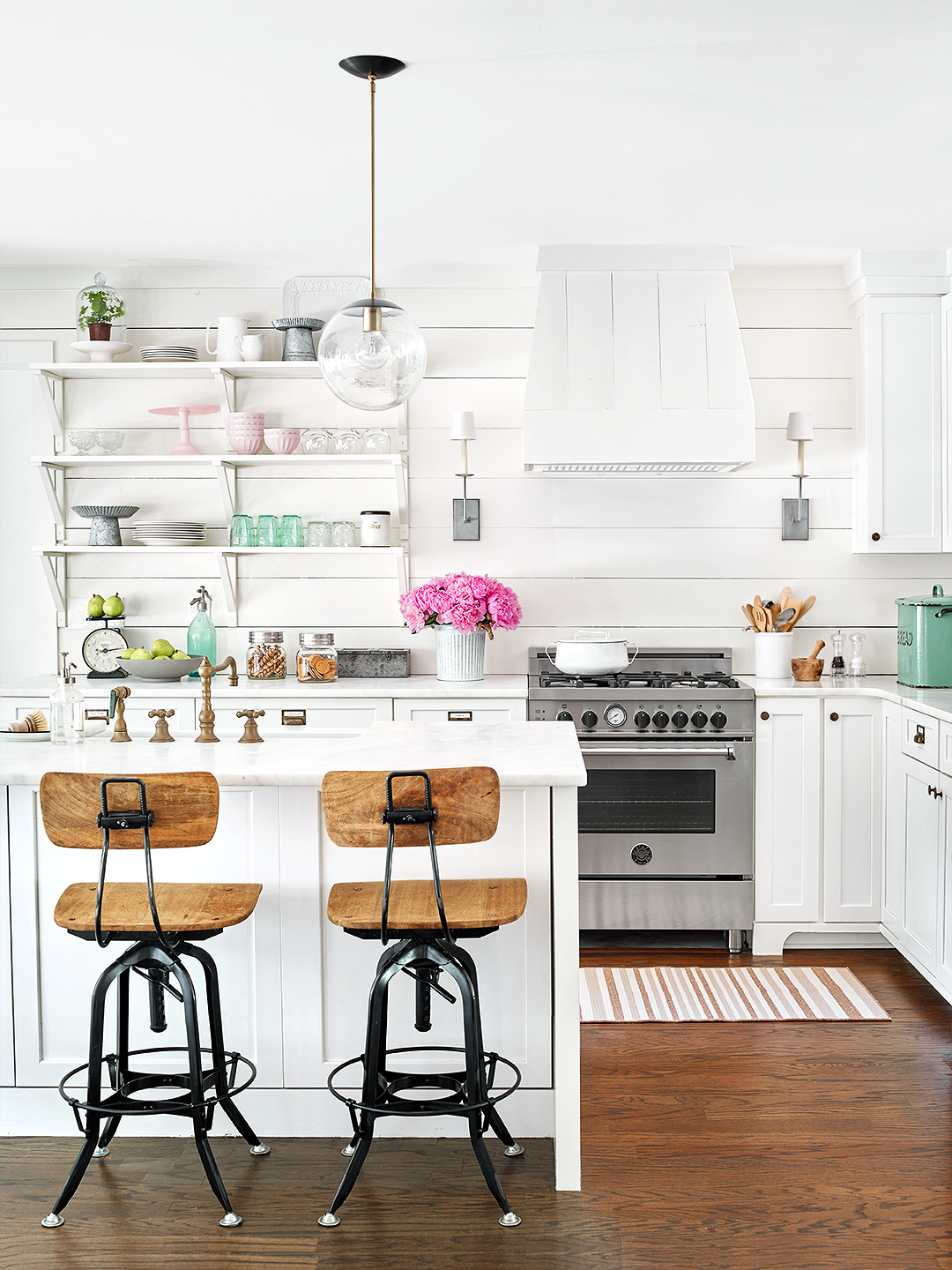 modern white farmhouse kitchen with dark wood floors bar chairs shelves