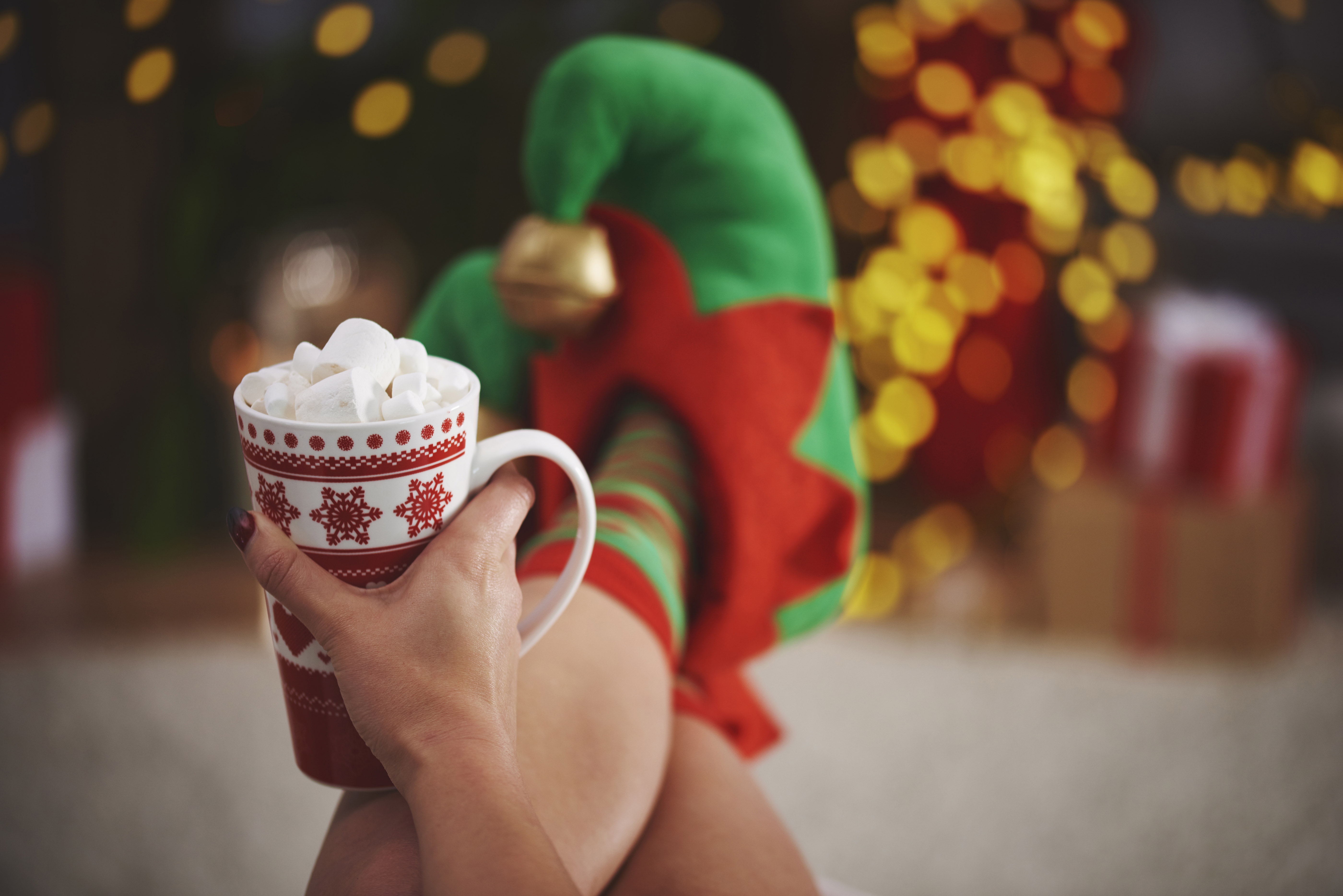 holding a mug of hot chocolate wearing elf slippers