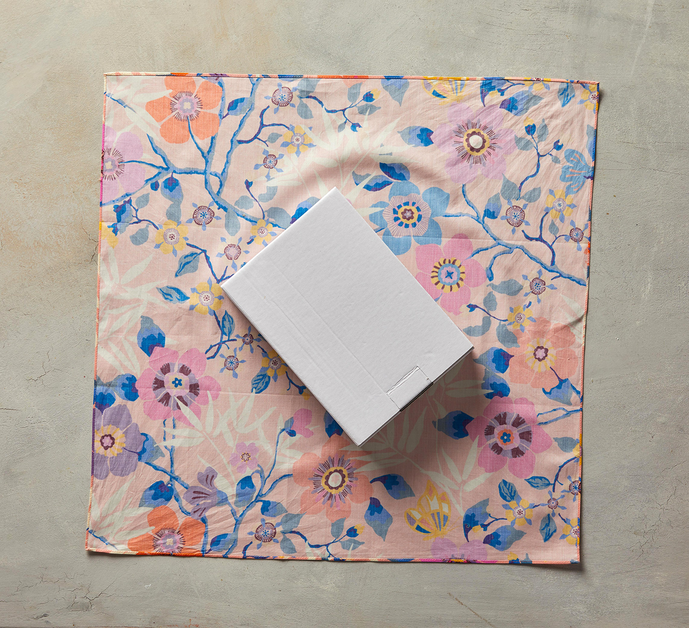 white box sitting diagonally on pink square fabric
