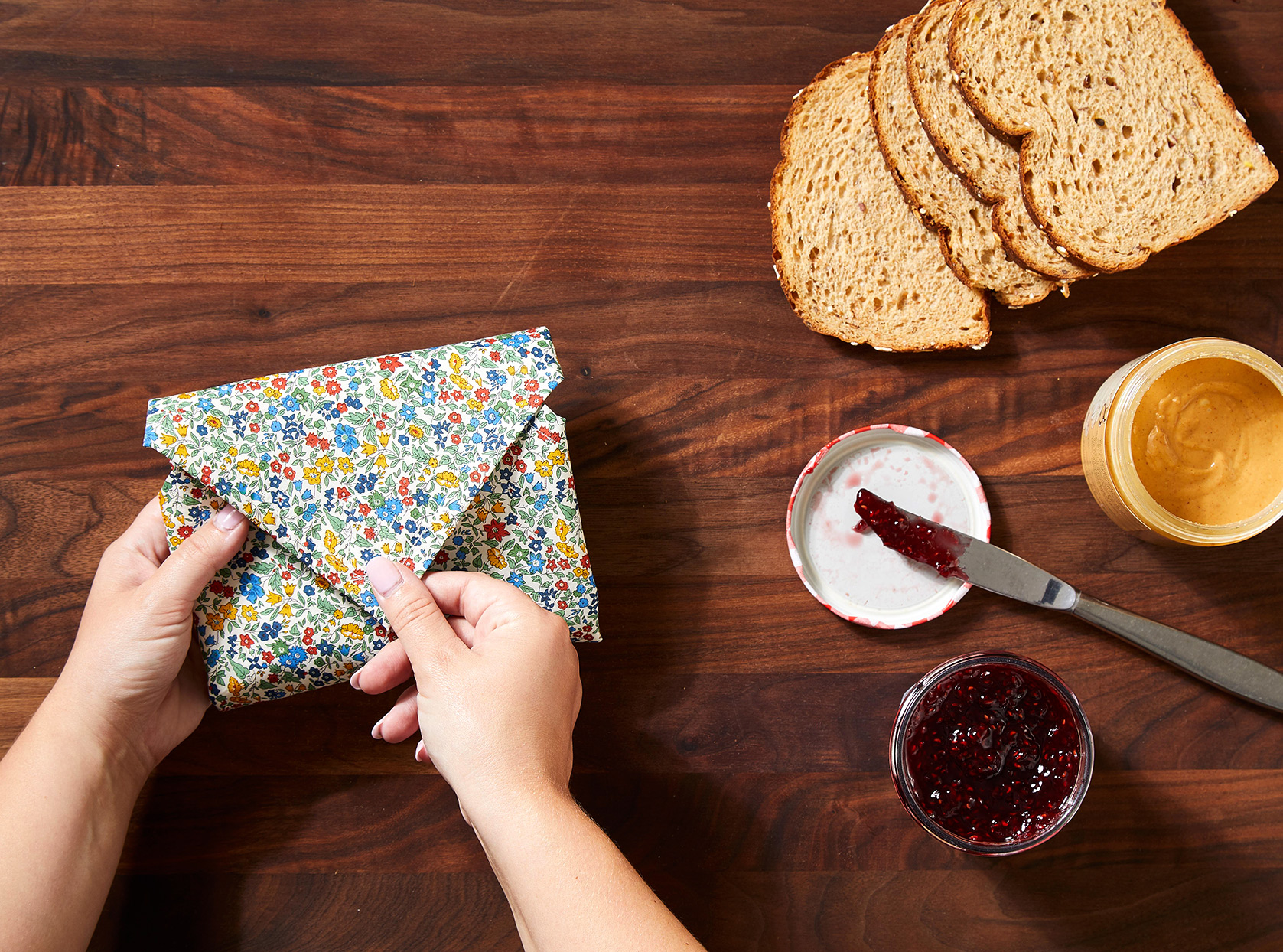 flowered sandwich pouch next to peanut butter and jelly makings