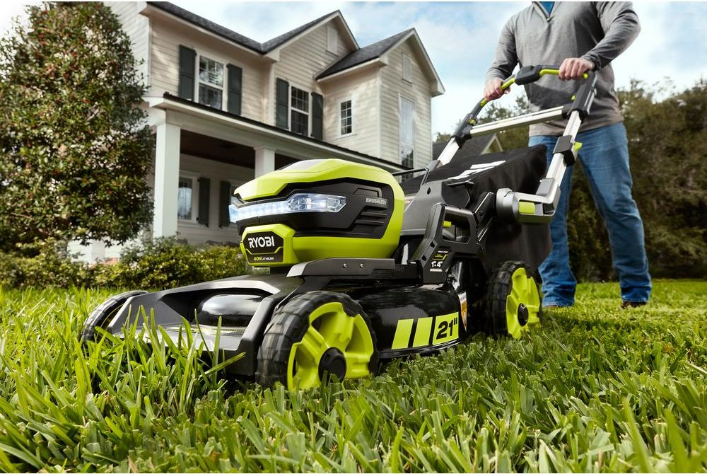 Man behind sel-propelled black and lime green Ryobi electric lawn mower
