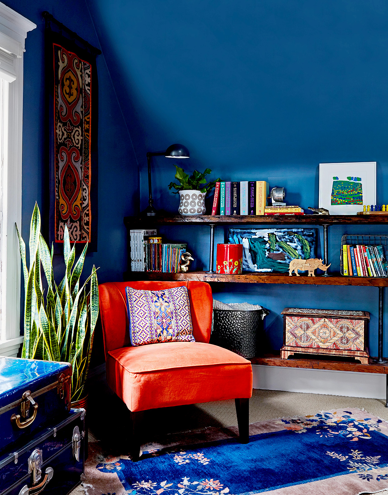 Dark blue walls with orange chair and shelving