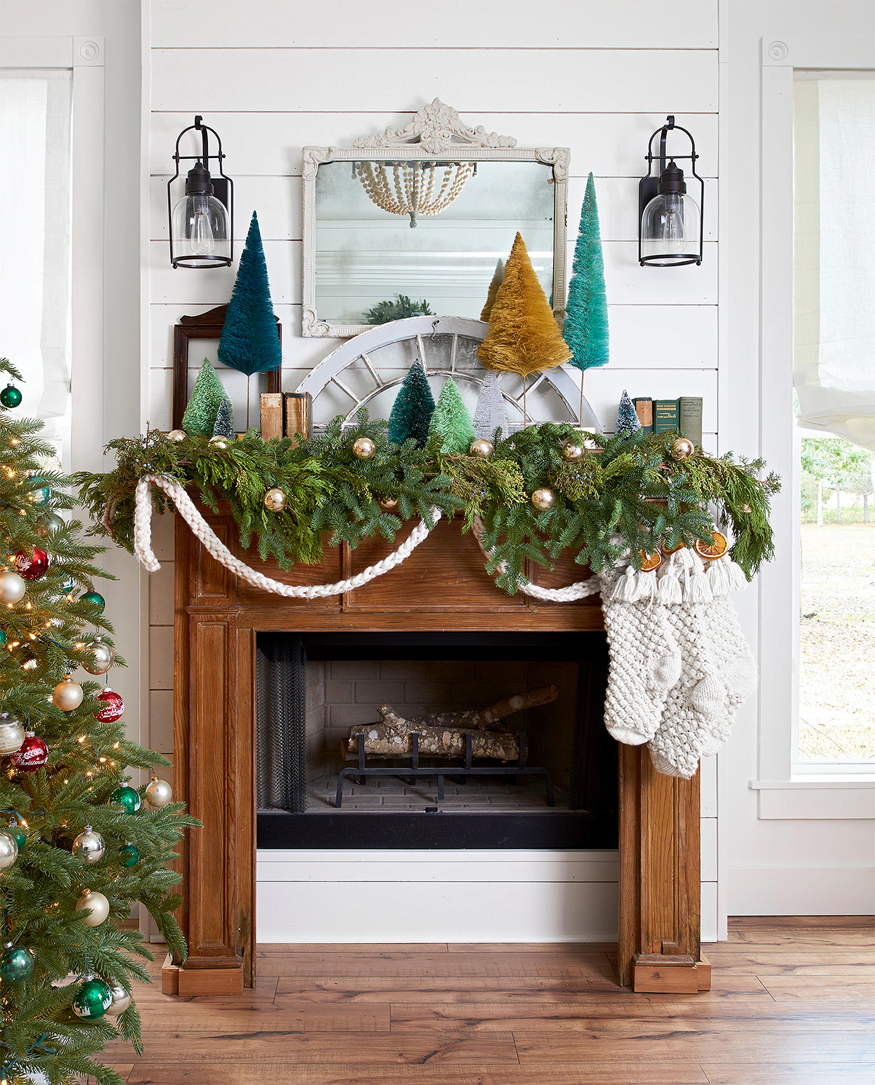 garland-covered mantel with knit Christmas stockings and trees