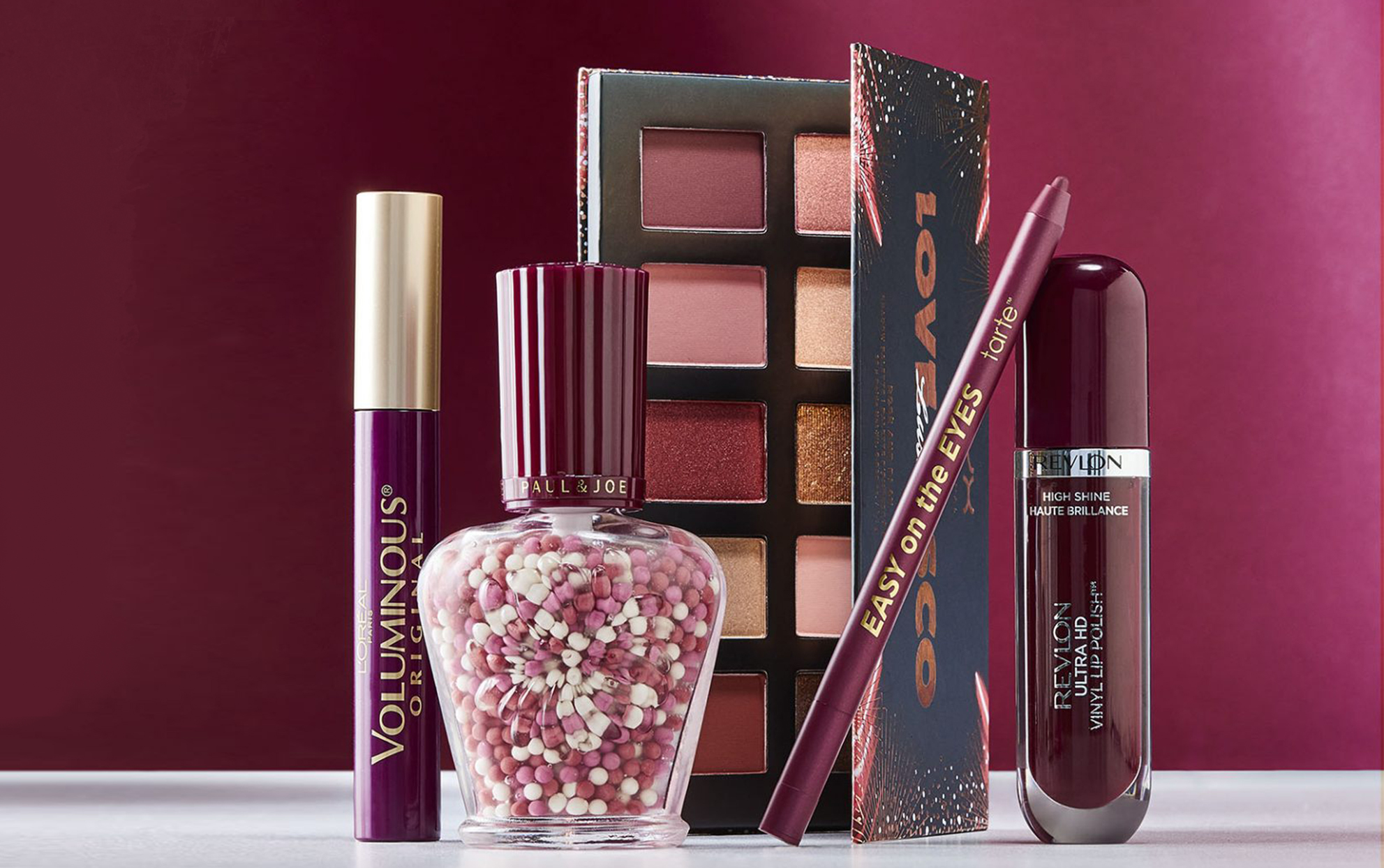 Several burgundy beauty products with a burgundy background on a white surface