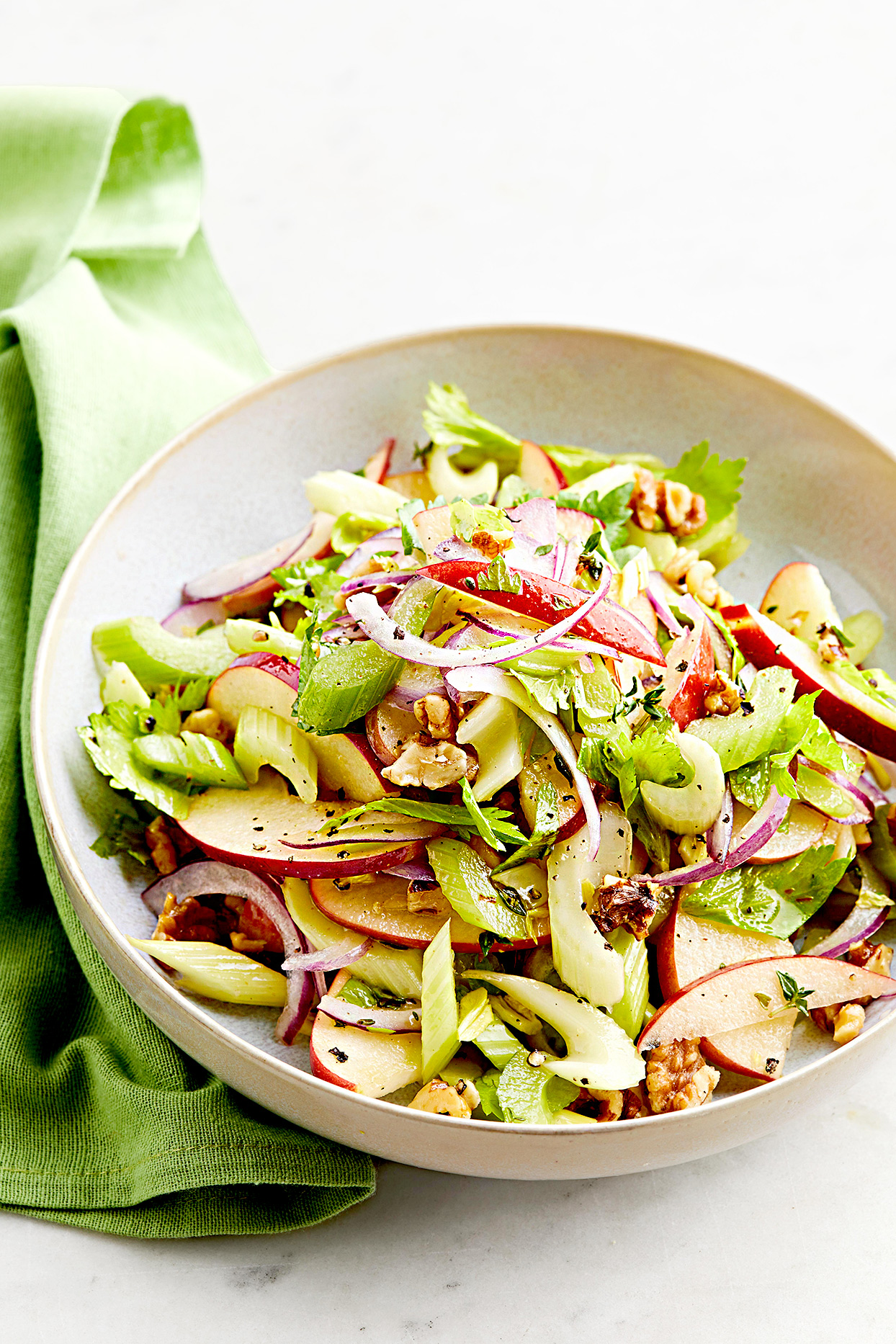 Overhead photo of bowl of celery and apple salad with walnuts