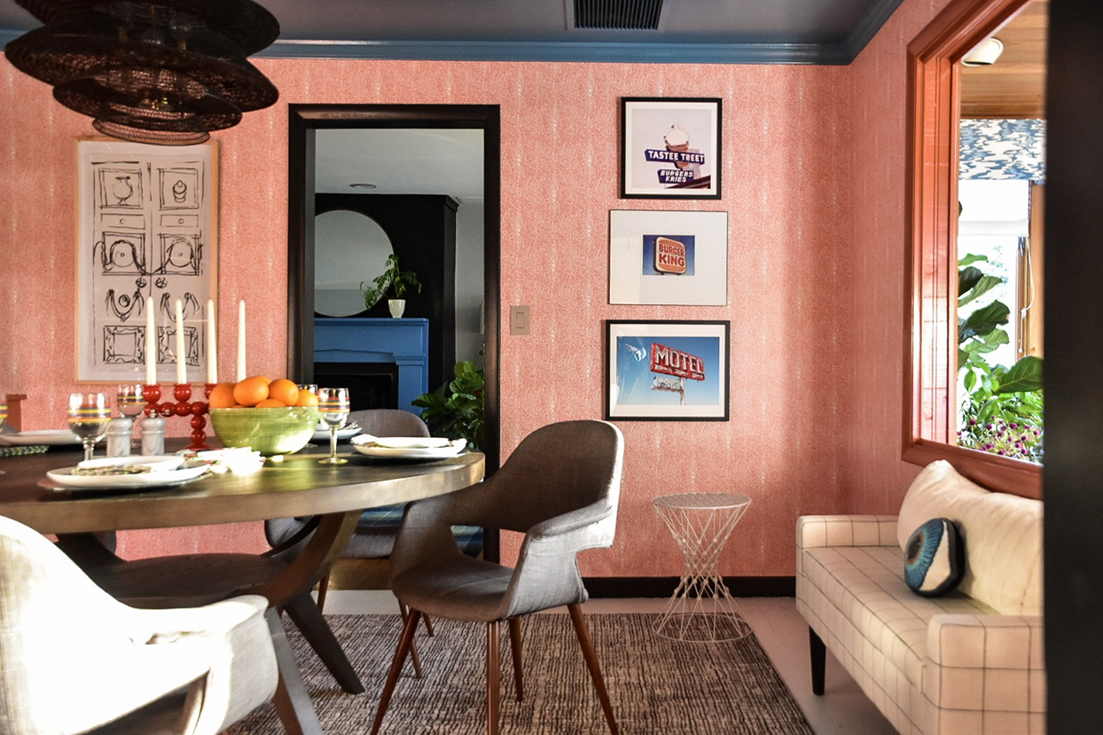 dining room with pink wallpapered walls table chairs and couch