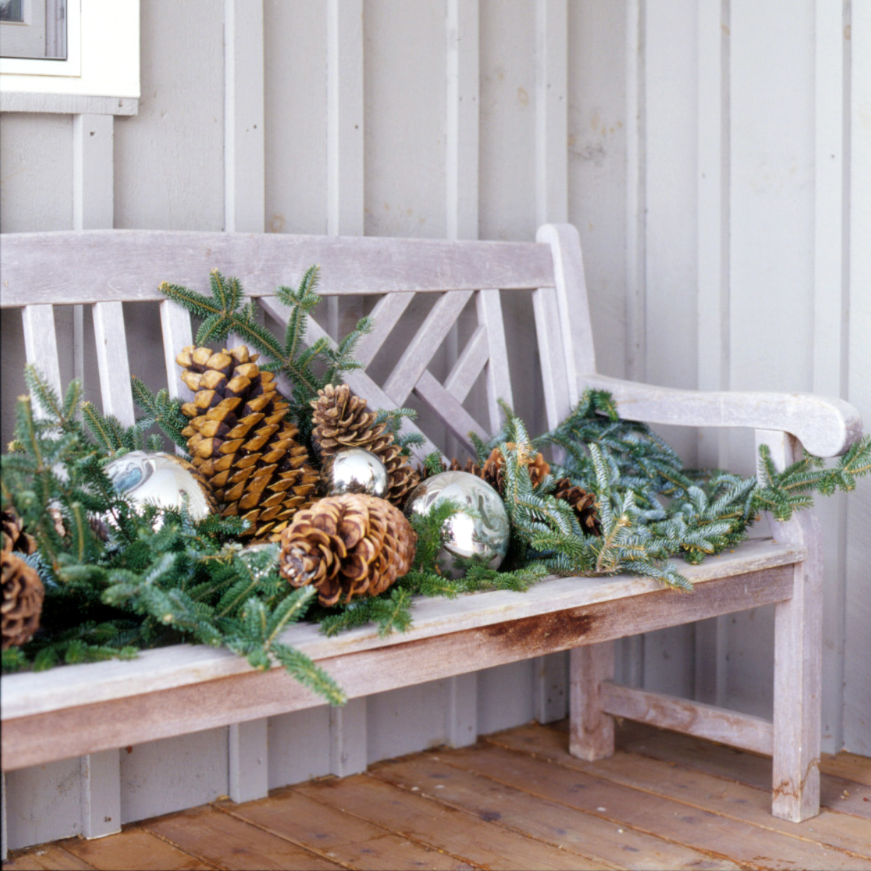 bench decorated with greenery pinecones and orbs