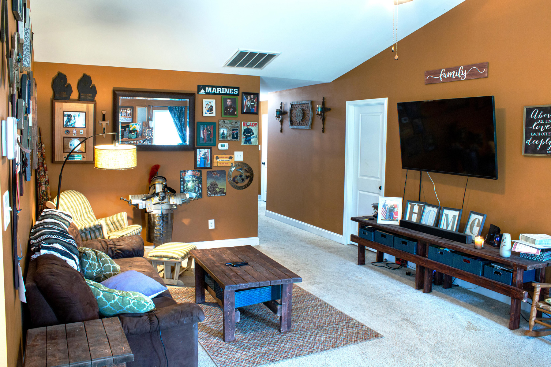 living room with orange walls couch chair and tv