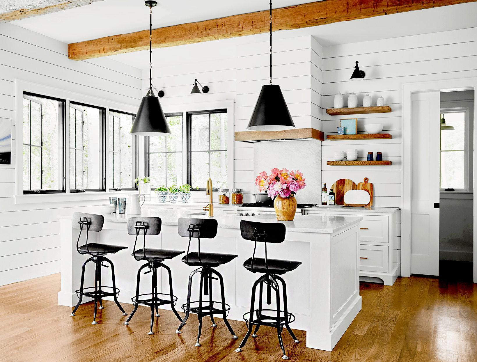 White kitchen with island and black stools