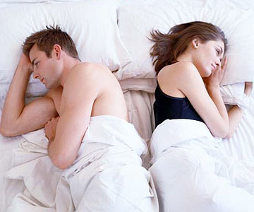 man and woman in bed together but facing opposite ways