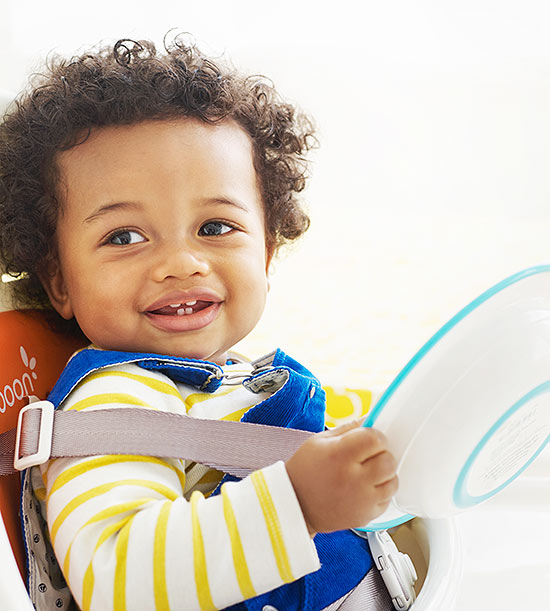 Baby in high chair holding plate