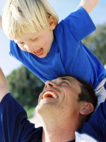 Dad outside with blond son over his head