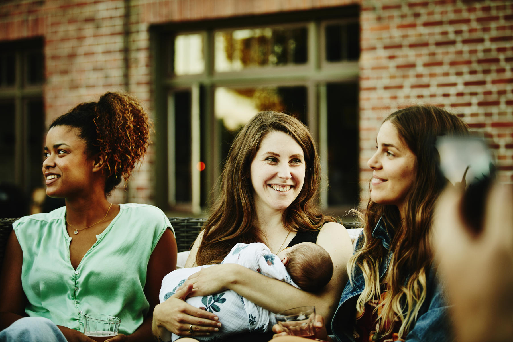 New mom holding baby while hanging out with friends