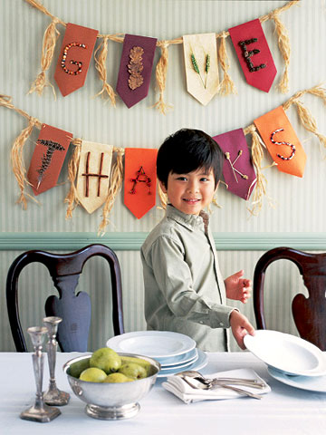 A boy in front of a banner for Thanksgiving.