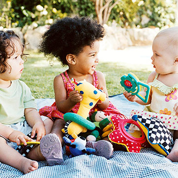three babies playing on blanket outside